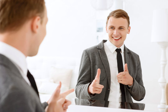 Man looking in mirror and pointing on himself