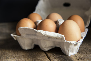Fresh eggs in egg box in moody natural lighting vintage retro st