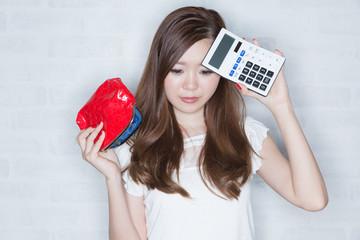 電卓と空っぽの財布 困る女性