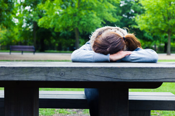 Sad young woman at table in park