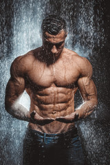 very muscular handsome athletic man in the rain