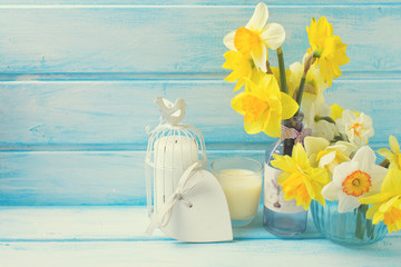 Narcissus in vases on wooden background