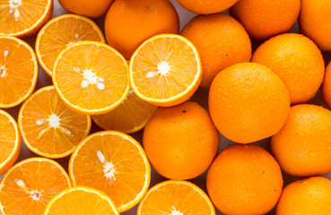 A closeup of a pile of oranges sliced and whole
