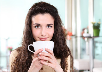girl smiling in coffee drink with cup in hand