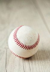 Old baseball on wooden background and highly closeup