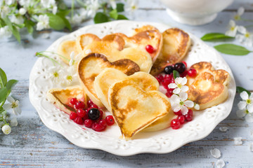 Heart shaped pancakes with berries of currant and honey
