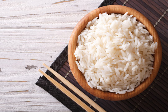 rice in a wooden bowl and chopsticks. horizontal top view
