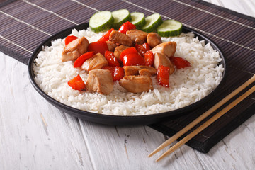 Rice with chicken pieces in a sauce close-up. Horizontal