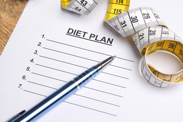 close up of paper with blank diet plan, pen and measure tape