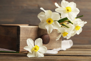 Fresh narcissus in chest on wooden background