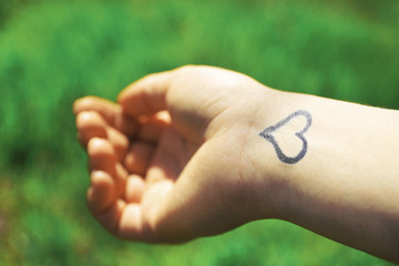 Hand of young woman with heart tattooed in it, on green nature background