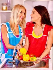 Women washing fruit at kitchen.