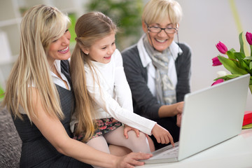 Cute girl using  laptop with mom and grandma