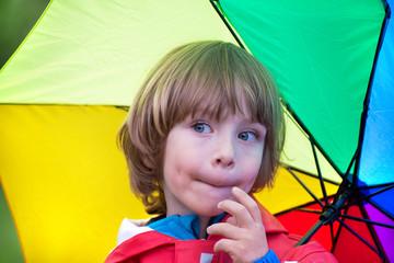 Little boy with umbrella in the rain