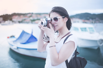 Attractive woman taking pictures with vintage retro camera laughing and smiling happy during summer holiday vacation travel.Seaside marine deck in Croatia.Island Korcula