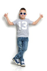 little boy in sunglasses standing and giving thumbs up sign