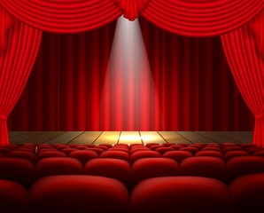 A theater stage with a red curtain, seats and a spotlight