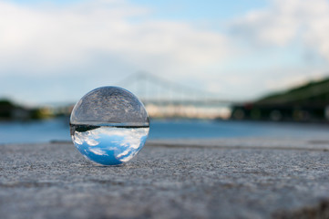 Glass transparent ball on bridge background and grainy surface