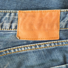 brown leather tag on blue jeans