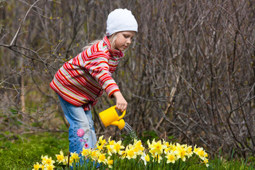 girl watering flowers with a watering-can