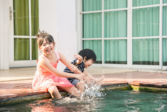 Asian children splashing around in the pool