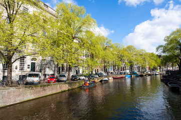 Amsterdam canal with boats along the river's bank in the spring.