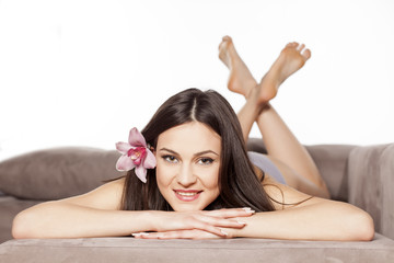 sensual woman with a flower in her hair posing on the bed