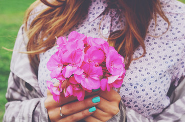 Stylish young woman holding bouquet of pink flowers in her hands