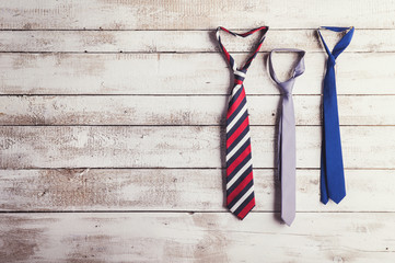 Fathers day composition of three ties on wooden background.