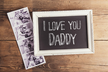 Picture frame and polaroid photos on wooden background.