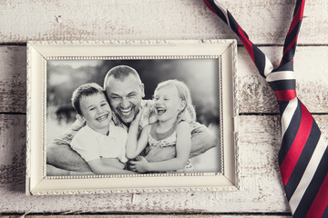Picture frame with family photo and a tie on wooden background.