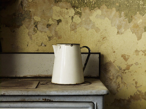 A vintage enamel jug of a traditional shape with a handle on an iron stove top.