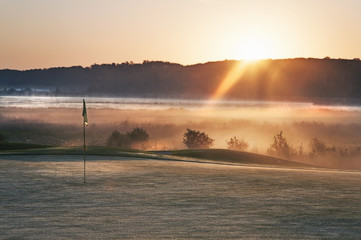 Glowing dawn light on a golf course green. The sun just appearing above a mountain range.