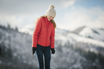 A young girl in a red coat and woolly hat outdoors in the winter.