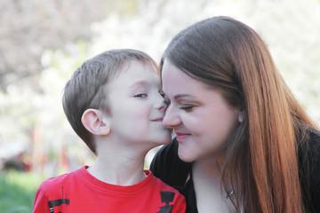 Little brothet kissing sister on cheek
