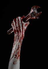 bloody hand holding a big wrench on a black background