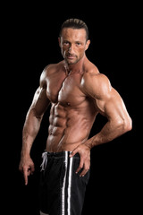 Muscular Bodybuilder Man Posing Over Black Background