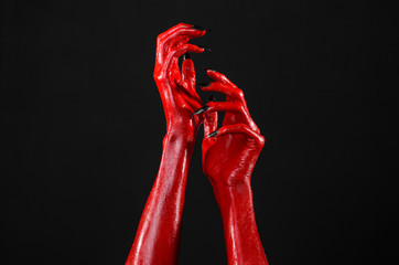 Red Devil's hands, red hands of Satan, black background isolated