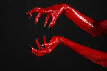 Red Devil's hands, red hands of Satan, black background isolated Fotoväggar