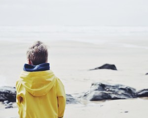 Rear view of boy in raincoat on the beach