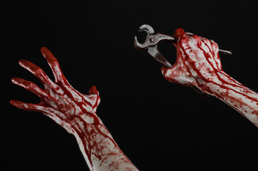 bloody hand holding a pliers on a black background