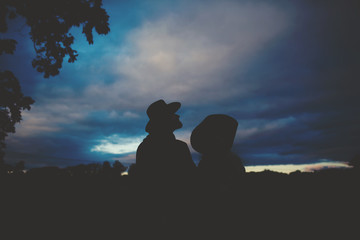 Couple wearing cowboy hats looking at night sky