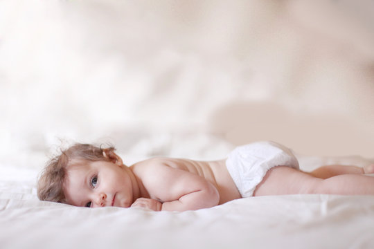 Side view of baby girl lying on bed