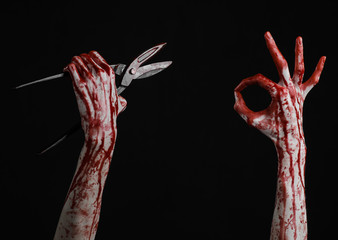 bloody hand holding a big old bloody scissors on a black