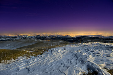 Snow sculpted by wind in a moonlit mountain scene at night.