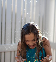 Girl (7-8) under spray of water outdoors