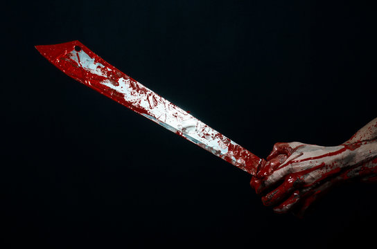 bloody hands holding a bloody machete isolated in studio