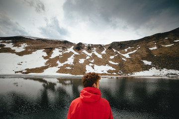 Back view of young man looking at mountain lake