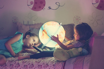 Girls looking at illuminated lamp in shape of globe while lying on bed in bedroom
