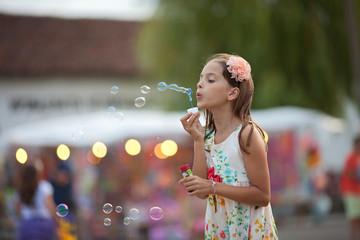 Girl (8-9) in dress blowing soap bubbles